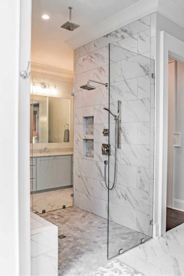 This his & her walk-in shower has a tall piece of clear glass on either side, but no door!