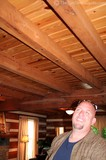 Jim admiring an upstairs log floor which becomes the ceiling for the room below it.