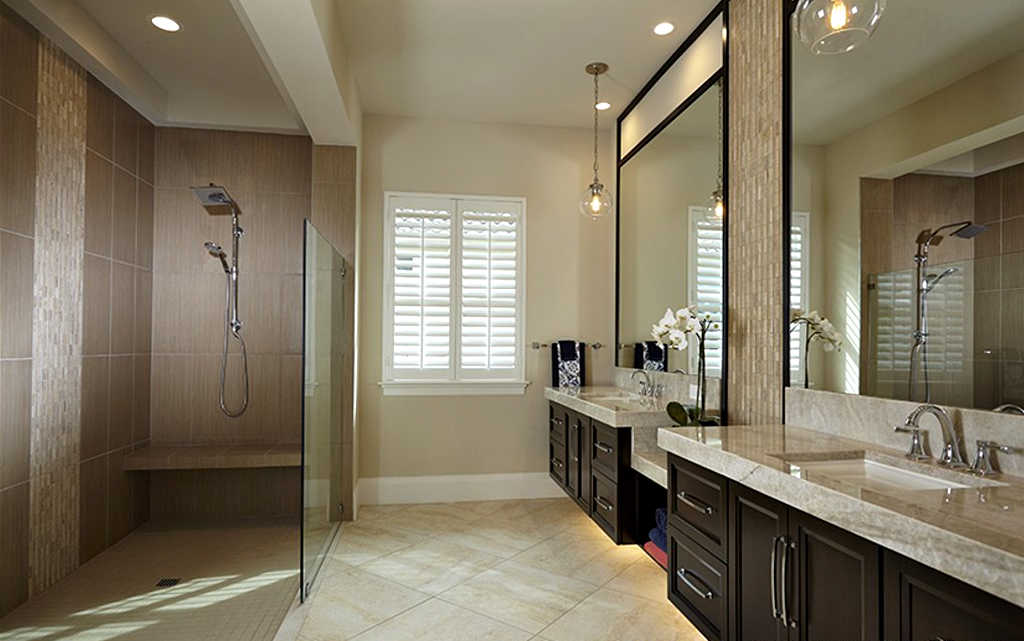 A doorless shower with a short glass wall in the master bathroom.