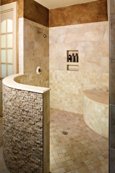 A doorless master shower with a curved rustic half wall.