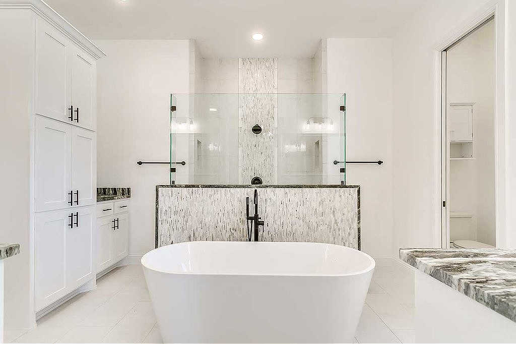 This is a super classy walk-thru shower for a master bathroom featuring a half-glass wall as the divider that separates the shower form the rest of the room.