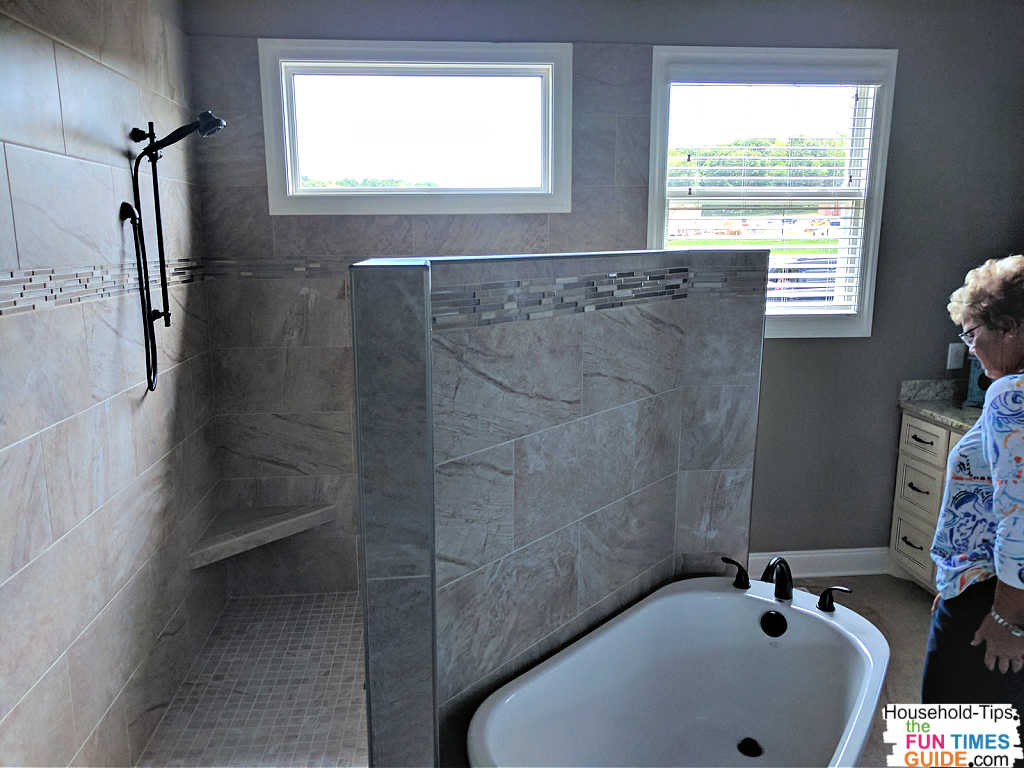 This doorless master shower uses a three-quarter height wall to separate the shower from the bathtub (and the rest of the room).
